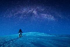 登山人在晚上爬上一个多雪的倾斜 免版税库存图片