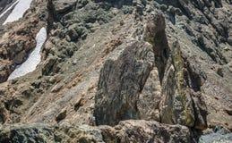 登山人坐式下降法入岩石地形 免版税库存图片