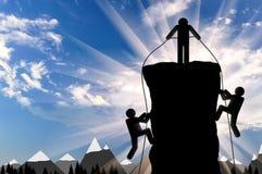 登山人帮助两个登山人上升在山上面的 免版税库存照片