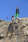 登山人帮助她的伙伴给富有山顶 库存图片