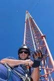 登山人投入在攀登塔的安全设备前 免版税图库摄影