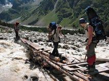 登山人穿过山河 高加索,俄国 免版税图库摄影