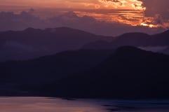 山剪影在下水上的 免版税库存图片