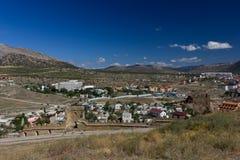 山包围的城市的看法 城市和古老堡垒的墙壁的顶视图 图库摄影