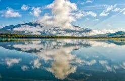 山反射在阿拉斯加的一个生动的蓝色冰河湖 库存图片