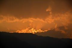 从山和云彩的日落光 免版税库存照片