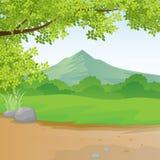 山和农村风景与草、布什和天空、云彩和农村道路 免版税图库摄影