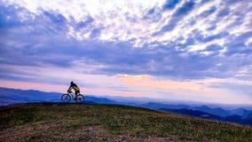 山和天空与云彩,全国自然公园背景的骑自行车的人  免版税库存照片