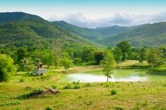 山和天空和池塘包围的议院 免版税库存照片