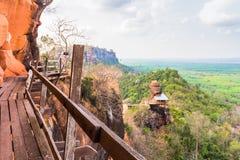 围绕山和寺庙的木足迹有在屋顶的岩石 免版税库存图片