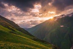山和小山惊人的风景在日落与五颜六色的天空在峰顶在Svaneti,乔治亚 在山的太阳光芒 免版税库存图片