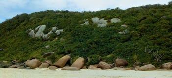 山和岩石由沙子海滩 免版税库存图片
