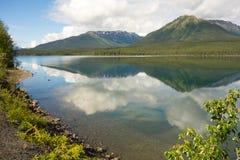 山和树在沿cassiar高速公路的一个镇静湖反射了 免版税图库摄影