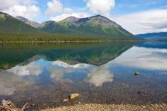 山和树在沿cassiar高速公路的一个镇静湖反射了 免版税库存图片