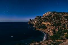 山和海在晚上在深蓝满天星斗的天空下 免版税库存照片