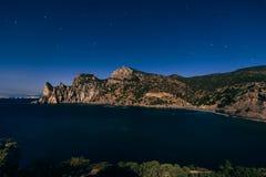 山和海在晚上在深蓝满天星斗的天空下 免版税库存图片