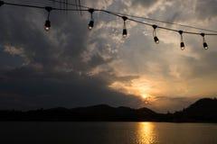 山和湖剪影晚上时间的与电灯泡 免版税库存图片