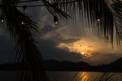 山和湖剪影晚上时间的与电灯泡 库存照片