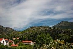 山和石头房子有红色屋顶的 免版税库存照片