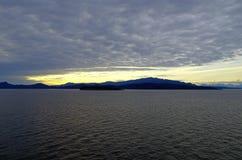 山和蓝色和黄色天空在太平洋 免版税库存图片