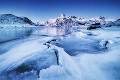 山土坎和冰冻结的湖表面上 在Lofoten海岛,挪威上的自然风景 免版税库存照片