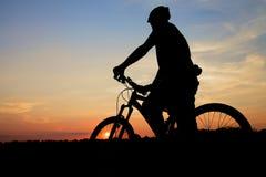 山在日落的骑自行车的人剪影 免版税库存图片