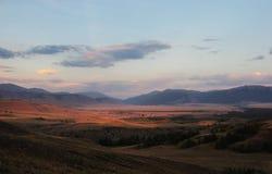 山在村庄的背景的干草原谷日落的 免版税库存图片