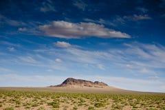 山在沙漠在蓝天下 免版税库存图片