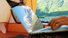 山在膝上型计算机屏幕被反射 自由职业者妇女使用计算机在旅游帐篷 股票视频