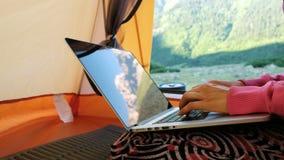 山在膝上型计算机屏幕被反射 自由职业者妇女在旅游帐篷使用计算机,键入在 股票录像