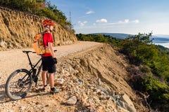 山在自行车的骑自行车的人骑马在海 库存照片