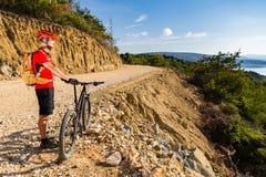 山在自行车的骑自行车的人骑马在海 免版税库存照片
