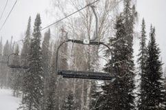 山在降雪的升降椅 库存照片