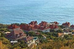 山坡的村庄镇在海的背景中 库存图片