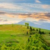 山坡草甸的村庄有山的森林的在日出 库存照片