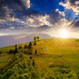 山坡草甸的村庄有山的森林的在日落 库存照片