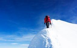 登山家伸手可及的距离多雪的山峰的山顶 概念:determin 免版税库存照片