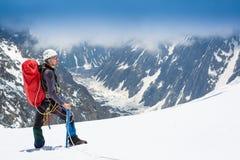 登山家到达一座多雪的山的上面 免版税库存照片