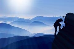 登山家攀登山顶 免版税库存图片