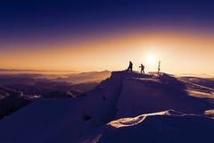 登山家日出雪山顶金黄黎明 免版税库存照片