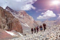 登山家走在离开的岩石地形的小组 库存图片
