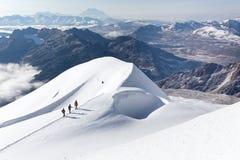 登山家走的上升的雪足迹山土坎,玻利维亚 免版税库存照片