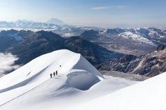 登山家走的上升的雪足迹山土坎,玻利维亚 免版税库存图片
