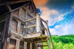 山小屋在背景风暴和闪电的阿尔卑斯 免版税图库摄影