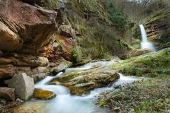山小河和逗人喜爱的瀑布在它` s圆形剧场 库存照片