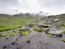 山小河和雪在欧特普罗旺斯加盖了高峰近的col de vars 库存图片