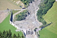 山小河鸟瞰图在与挖掘机和卡车工作的巨型的泥流以后被阻拦的奥地利阿尔卑斯清扫 免版税库存照片