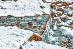 山小河冻瀑布在雪和ro中间的 免版税库存照片