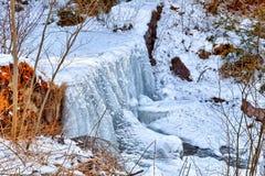 山小河冻瀑布在雪和ro中间的 图库摄影