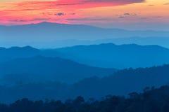 山层数在薄雾的在与灼烧的天空的日落时间, 图库摄影